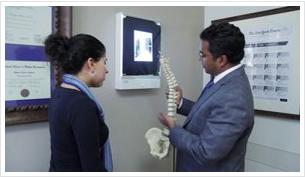 neurosurgeon holding spine and explaining to woman